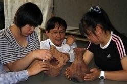 本物の土器に触っている子供たちの写真